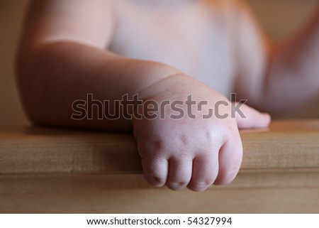 Sweet 6 month old Baby Boy's Hand on crib - stock photo