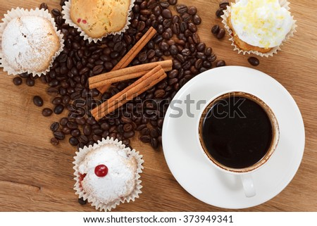 Sweet muffin and Coffee beans on wooden background, tasty breakfast. Closeup. - stock photo