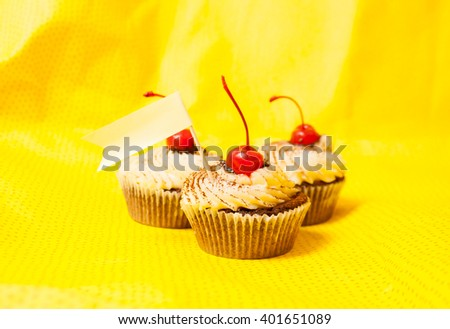 Sweet muffins with cherry on yellow background