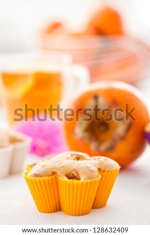 sweet muffins with persimmon slices and nuts - stock photo