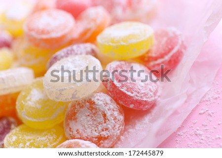 Sweet  multicolor candies on paper, on color background - stock photo
