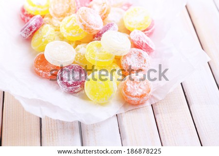 Sweet  multicolor candies on paper, on  color wooden background - stock photo