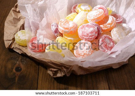 Sweet  multicolor candies on paper, on wooden background - stock photo