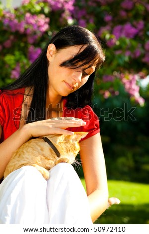 Sweet natural woman relaxing weekend in garden with pet cat - stock photo