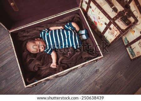 Sweet newborn baby sleeping in box on blanket - stock photo