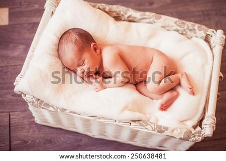 Sweet newborn baby sleeping in wicker basket - stock photo