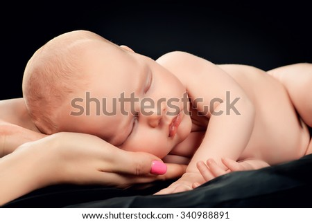 Sweet newborn baby sleeping on mother's hands. Love and tenderness. Black background.