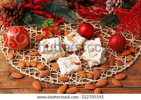 Sweet nougat with almonds and Christmas decoration table close up