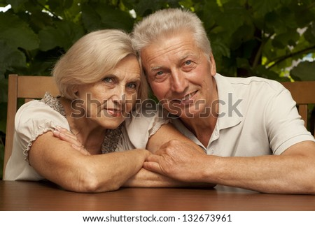 Sweet older couple sitting at a table at home on the veranda - stock photo