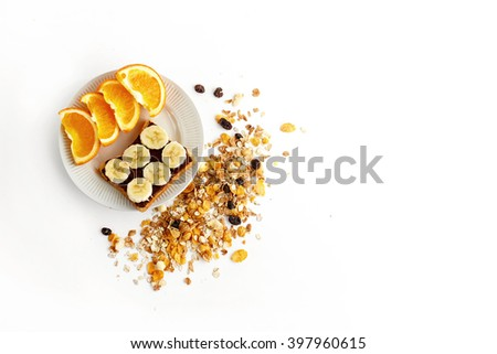 sweet oranges and banana on bread with chocolate and granola on white background, delicious healthy breakfast concept - stock photo