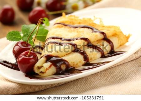 Sweet pancake with chocolate sauce and cherries - stock photo