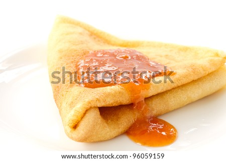 sweet pancakes with apricot jam on a white plate - stock photo