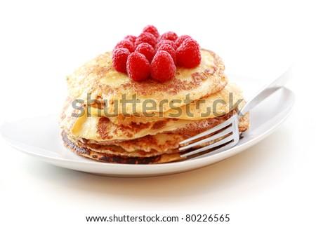 Sweet pancakes with fresh raspberries on white background - stock photo