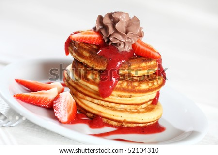 Sweet pancakes with strawberry sauce and chocolate cream - stock photo