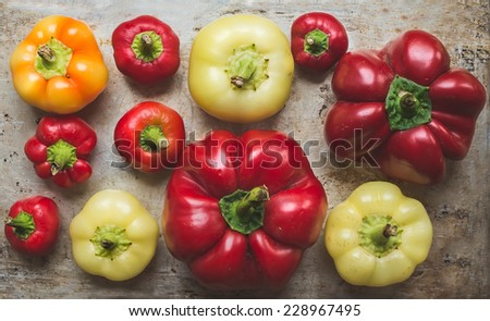 Sweet paprika of different size and color on a rustic metal cooking surface  - stock photo