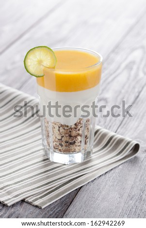 Sweet peach mousse with organic yoghurt served in panna cotta way. Fresh fruit and grain dessert decorated with lime slice. - stock photo