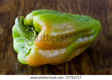 Sweet pepper lying on the wooden desk - stock photo