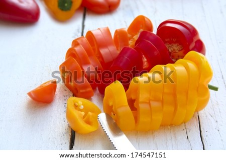Sweet peppers sliced in pieces with knife on white wooden background