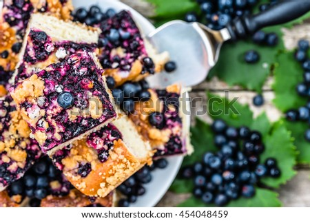 Sweet pie baked with blueberry fruits on yeast dough, pieces on plate, top view - stock photo