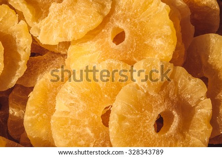 Sweet Pineapple - Dried candied pineapple rings in a full frame composition. Sweet slices of  fruit in a warm yellow color under a bright sun on a market stall. - stock photo