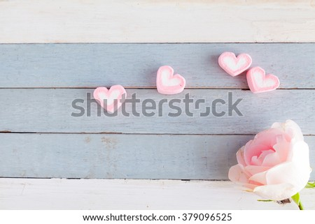 sweet pink heart marshmallow with pink rose on vintage blue and white wood background