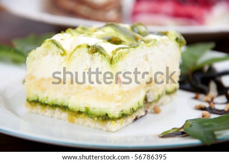 Sweet pistachio dessert with vanilla cream and nuts and chocolate on white plate with juice. - stock photo