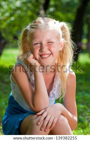 Sweet, playful blond girl sitting in the green garden and backing chin in his hand - smiles and winks. On its face a lot of freckles