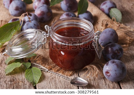 Sweet plum marmalade in a glass jar on the table close-up. horizontal - stock photo