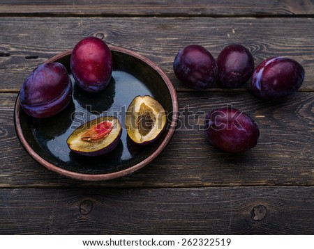 Sweet plums on dark wooden background - stock photo