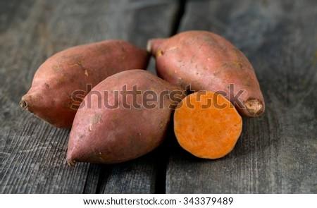 sweet poato on wooden surface - stock photo