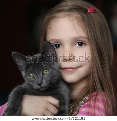 Sweet portrait of a cute little girl holding and snuggling a gray kitten - stock photo