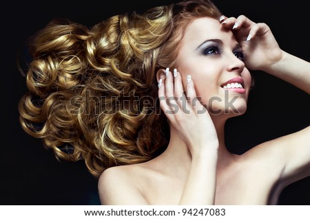 sweet portrait of an attractive young blond girl with wavy hair and well done nails lying down on black background - stock photo