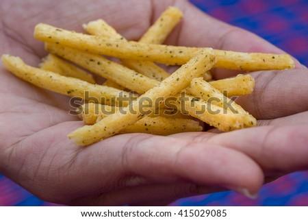 Sweet potato chips in hand - stock photo
