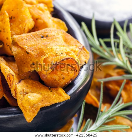 Sweet potato crisps or chips with rosemary and sea salt.   - stock photo