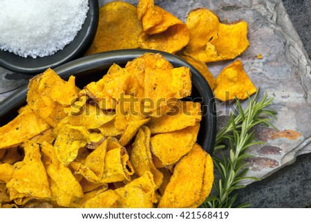 Sweet potato crisps or chips with rosemary and sea salt.  Overhead view. - stock photo