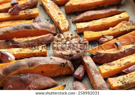 Sweet potato roasted chips just taken from the oven. - stock photo
