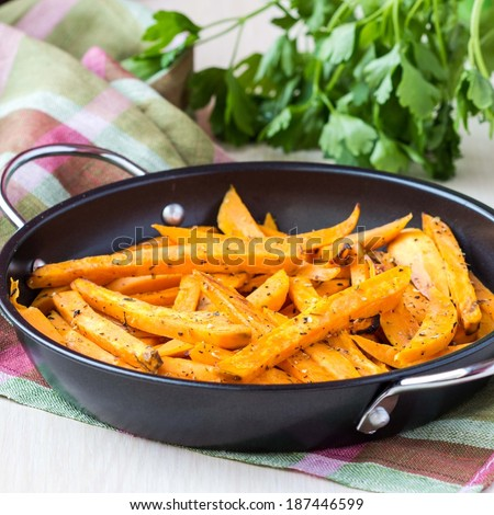 Sweet potatoes, batata, sliced, fried in pan with spices, herb - stock photo