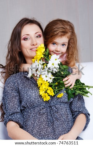Sweet preschool girl embracing mom and presenting her flowers bunch - stock photo