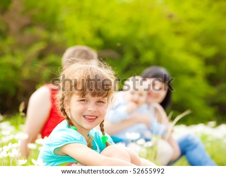 Sweet preschool girl on the meadow, parents and little brother behind