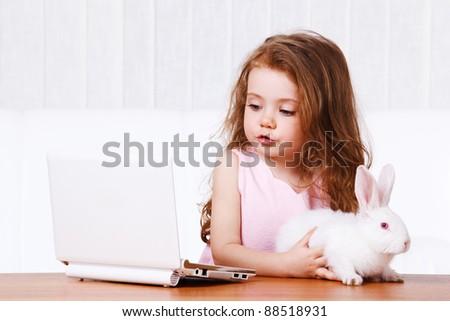 Sweet preschool girl with laptop and bunny - stock photo