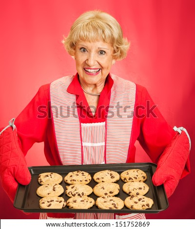 Sweet pretty grandmother holding a tray of freshly baked chocolate chip cookies.