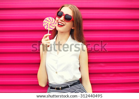 Sweet pretty young woman with lollipop over pink background - stock photo