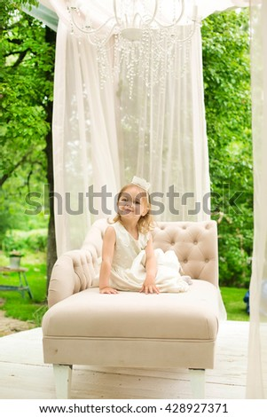 sweet princess girl with crown in the garden - stock photo