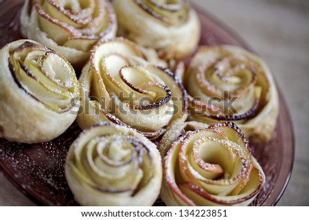 Sweet puff pastry roses with powdered sugar - stock photo