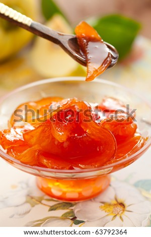 Sweet quince jam in glass dish with spoon - stock photo