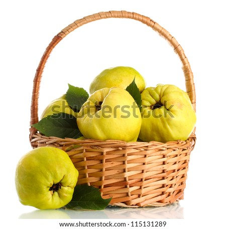 sweet quinces with leaves in basket, isolated on white - stock photo