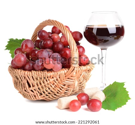 Sweet red grapes in wicker basket and glass of wine isolated on white - stock photo