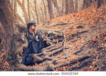 Sweet red-haired girl in black beautiful witches and magic cap sits on a mighty tree roots in the October autumn forest, strewn with fallen leaves, Halloween