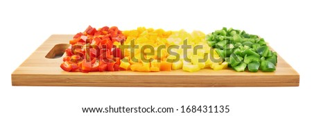 Sweet red, orange, yellow and green bell pepper cut in pieces over a wooden cutting board, isolated on a white background - stock photo