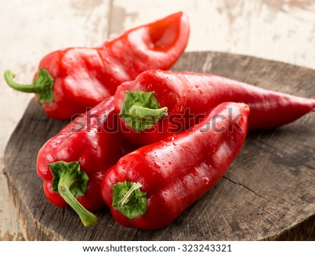sweet red pepppers on wooden surface